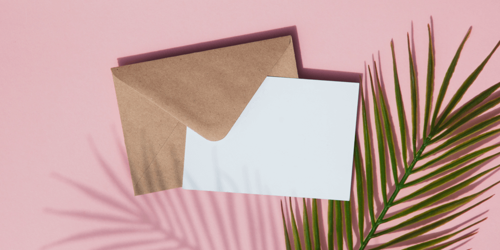 Blog Header Image for How to Add a Contact Button to Instagram - envelope, card and palm leaf on pink background